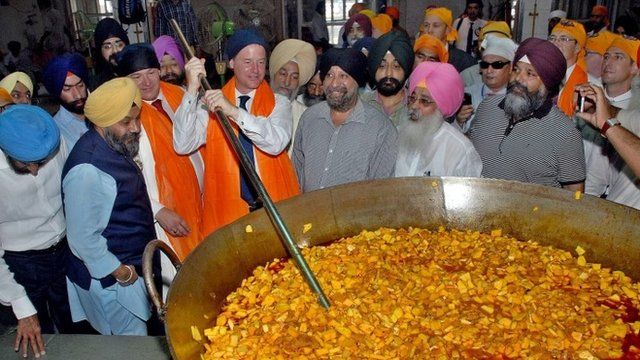 Nick Clegg stirring a curry in India