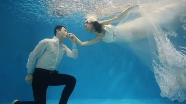 A groom kissing his bride's hand in an underwater photo shoot