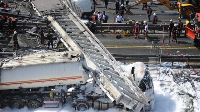 Rescue workers try to clear the area after a pedestrian bridge collapsed after it was hit by a fuel tanker on a main highway in Istanbul, Turkey 03 September 2014