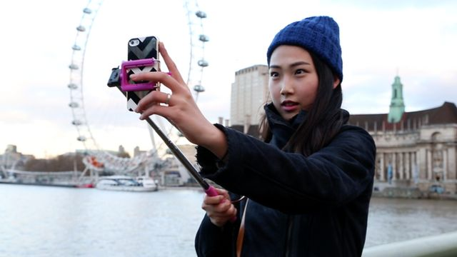 A young woman takes self-portrait with a selfie stick in central London