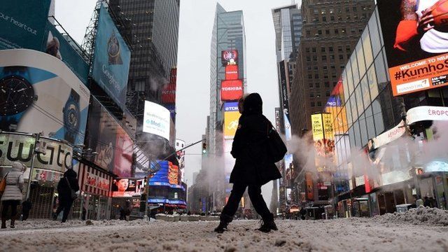 """A few tourists wonder around nearly deserted New York""""s Times Square what is normally a crowed morning rush hour"""