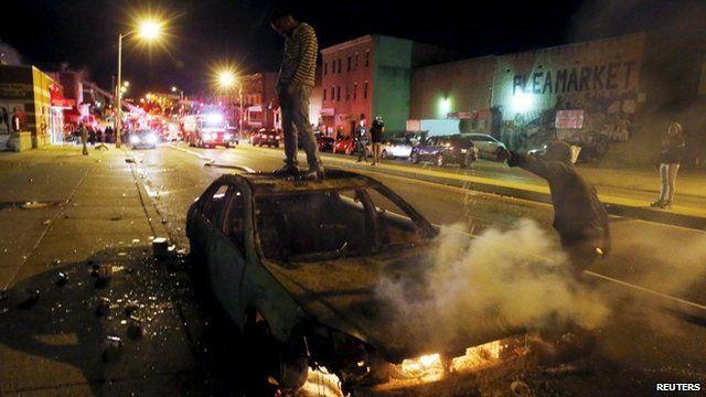 A rioter stands atop a burning car