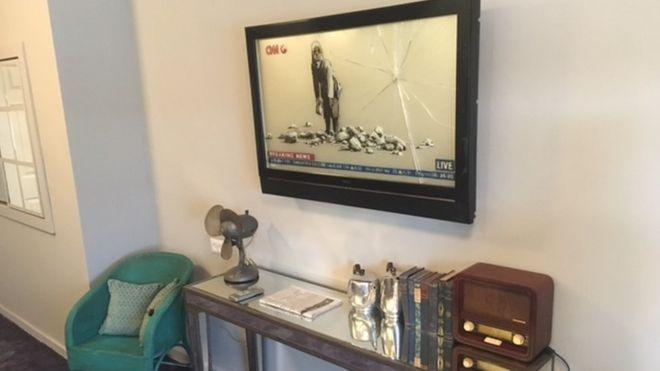 Un dibujo de una niña dentro de un televisor tirando una piedra contra la pantalla.