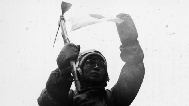 Portrait of Japanese mountaineer Junko Tabei giving a climbing demonstration next to a rubble pile, outside Frankfurt Station, circa 1975