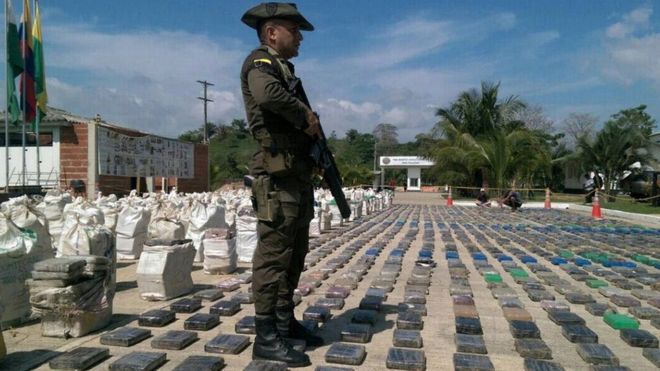 Colombian police officer guards confiscated packages of cocaine in Turbo, Colombia, 15 May 2016