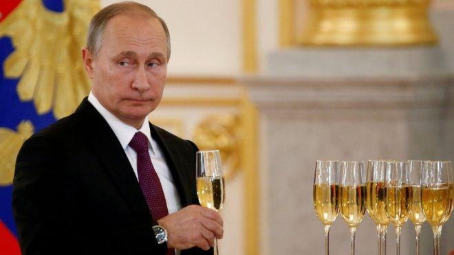 Vladimir Putin segura taça de espumante