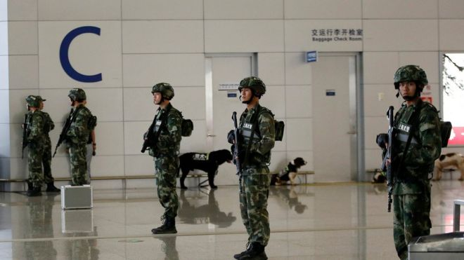 Paramilitary policemen stand guard near the site of a blast at a terminal in Shanghai's Pudong International Airport 12 June 2016