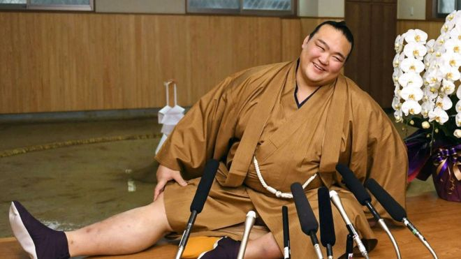 New Year Grand Sumo Tournament winner Kisenosato Yutaka stretches his legs during a press conference at his Tagonoura stable in Tokyo on 23 January 2017