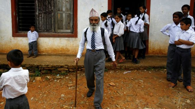 Durga Kami walks outside his school