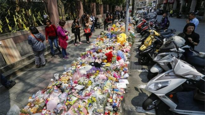 People offer flowers and prayers for a four-year-old child victim of a random killing, at a makeshift memorial at a street next to the crime scene, in Taipei, Taiwan, 29 March 2016.