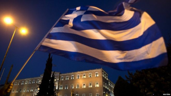 The Greek parliament is seen behind a flag during an anti-austerity rally in Athens, Greece 22 July 2015.