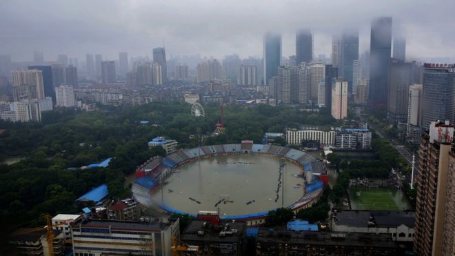 Wuhan - in foreground, flooded stadium, in background, skyscrapers covered in fog