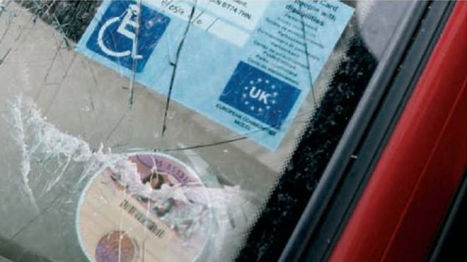 A smashed windscreen on a car with a disability badge