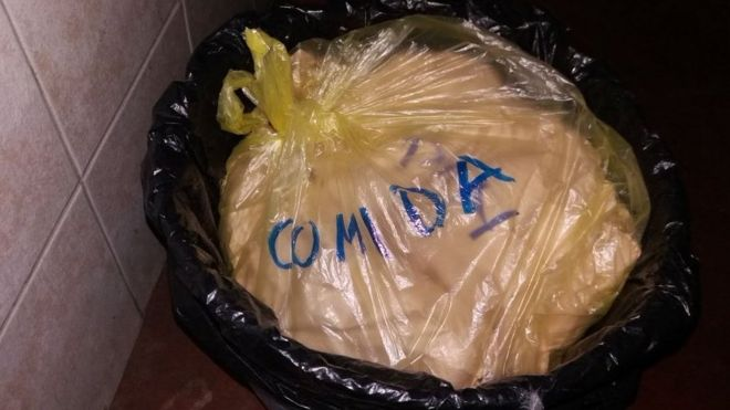 "A bag of food waste in a bin labelled ""food""."