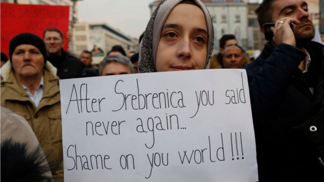 "A Bosnian woman holds a banner during a solidarity rally in Sarajevo, Bosnia on 14 December, saying: ""After Srebrenica you said never again. Shame on you, world""."