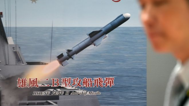 A man walks past a poster showing a home made Hsiung Feng II anti-ship missile during a press conference of the 2015 Taipei Aerospace and Defense Technology Exhibition at the World Trade Center in Taipei on August 12, 2015