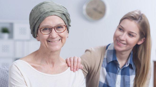 Mulher com câncer ao lado de outra mulher