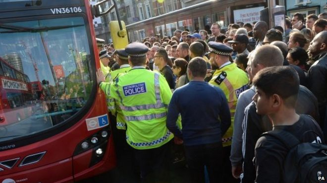 Police helping huge crowds of people to get on buses