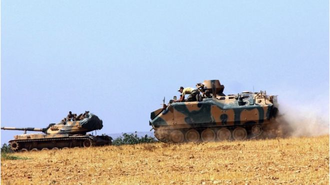 A Turkish army tank and an armoured vehicle are stationed near the border with Syria