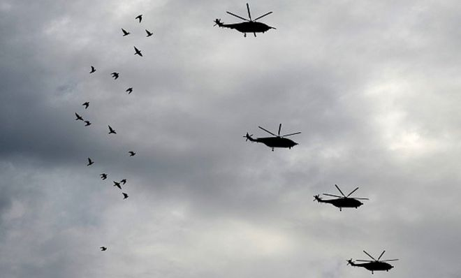 Chinese military helicopters, taking part in a rehearsal ahead of a military parade to mark the 70th anniversary of the end of World War II, fly over a flock of birds, in Beijing on August 23, 2015