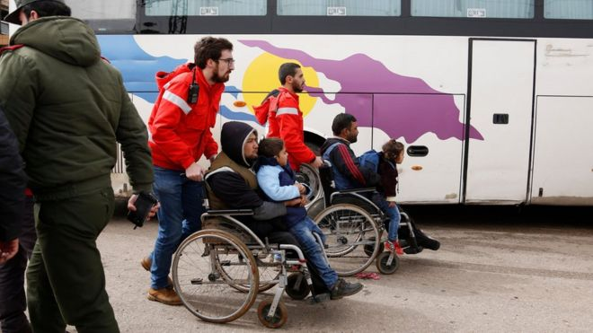 Members of the Syrian Arab Red Crescent assist the families of opposition fighters, board a bus during a government-led evacuation from the rebel-held al-Waer neighborhood, in the western outskirts of the central city of Homs, Syria, 18 March 2017