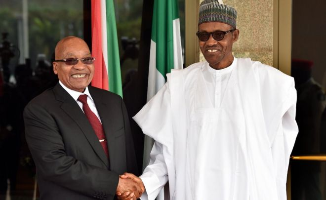 South African President Jacob Zuma (L) being welcomed by Nigerian President Muhammud Buhari (R) during the official welcome ceremony at the State House in Abuja, Nigeria