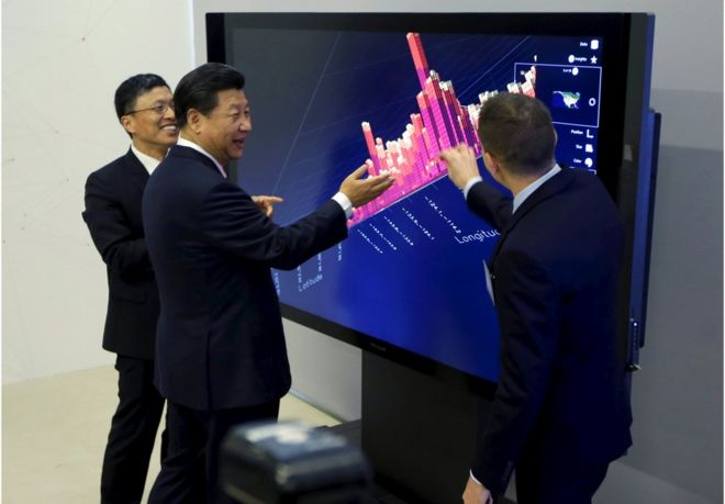 Chinese President Xi Jinping (C), Microsoft's Harry Shum (L) and David Brown (R) take part in a demonstration of how Microsoft Surface technology can be used for data visualization during Xi's tour of Microsof's main campus in Redmond, Washington 23 September 2015