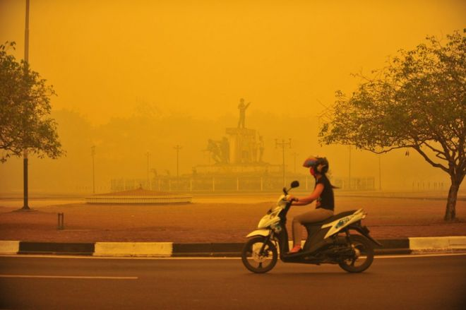 An Indonesian woman rides a motorbike amid thick yellow haze in Palangkaraya, Central Kalimantan province, Indonesia, 23 October 2015.