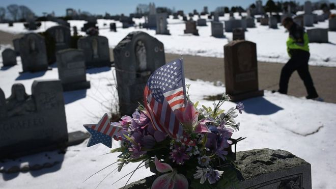 An American flag and flowers on a grave in Gloucester, Massachusetts