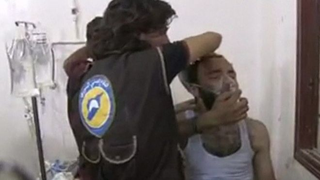 A man breaths into a mask, the supposed victim of a gas attack in Syria