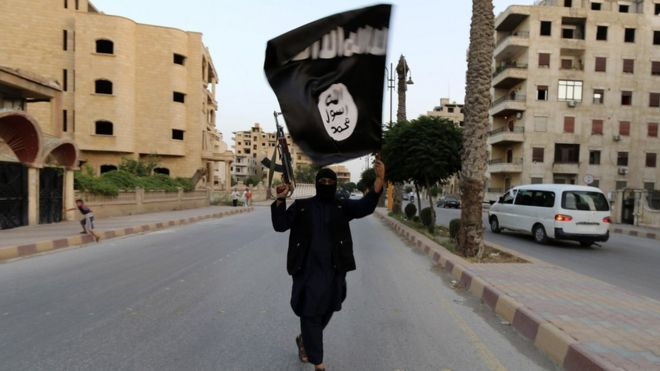 A lone armed and masked Islamic State militant waving an ISIS / ISIL flag, on a deserted street in Raqqa, June 2014