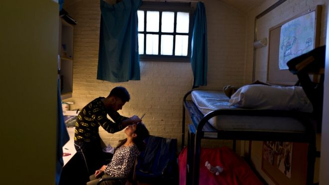 Yazidi refugee Yassir Hajji, 24, from Sinjar, Iraq, adjusts the eyebrow of his wife Gerbia, 18