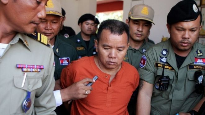 Yem Chrin (C) is escorted by Cambodian police officials in Battambang province, western Cambodia, on 3 December
