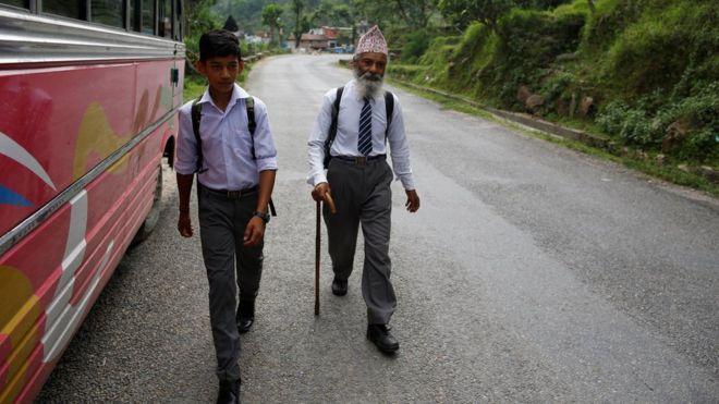 Mr Kami walks with his classmate Sagar Thapa