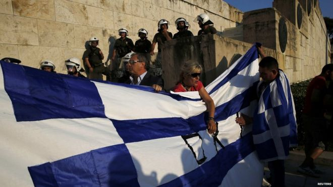 Protesters hold a Greek flag in front of the parliament building during an anti-austerity rally in Athens