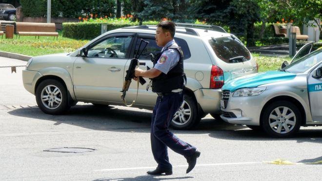 A policeman runs across the street in Almaty