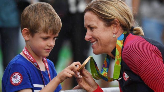 La ciclista estadounidense Kristin Armstrong le muestra su medalla de oro a su hijo.
