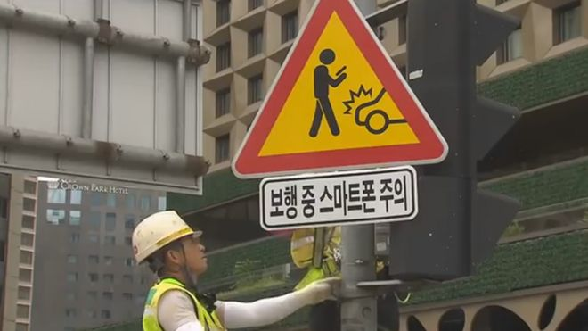 A workman installing one of the signs