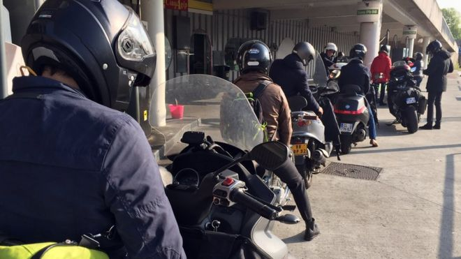 nine motorbike riders queue at a petrol station