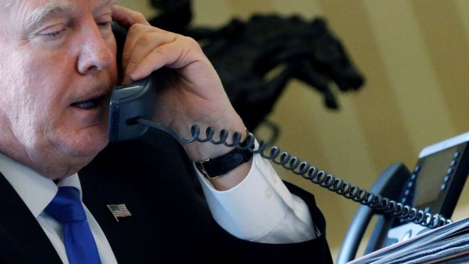 US President Donald Trump speaks by phone in the Oval Office at the White House in Washington, 28 January 2017