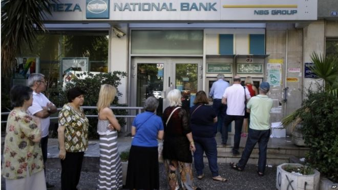 "People stand in a queue to use an ATM outside a closed bank, next to a sign on the plant, bottom right, reading """"NO"""" in Athens, Tuesday, June 30, 2015."