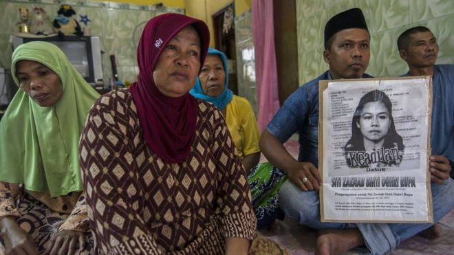Family members of beheaded Indonesian maid Siti Zainab hold up a poster (R) bearing her portrait at their family home in Bangkalan in East Java province on 15 April 2015