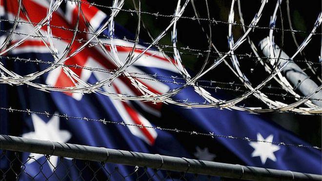 Australian flag behind razor wire