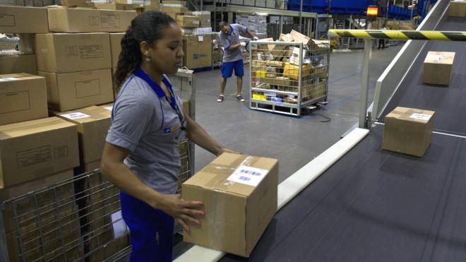 Funcionária dos Correios segura encomenda em depósito em São Paulo