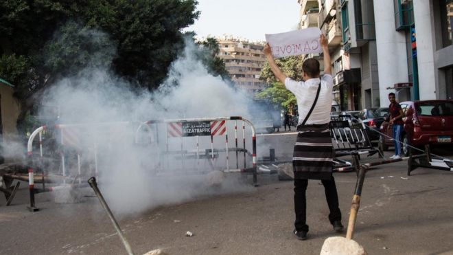 An anti-government protester holds a placard near tear gas fired by policemen during a protest in Cairo, Egypt, 25 April 2016.