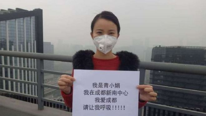 """Qing Xiaojuan took part in the online protest campaign. The board she's holding reads: """"I love Chengdu. Please let me breathe!"""""""