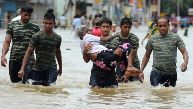 A member of a Sri Lankan Army rescue team carries a woman to safety through floodwaters in the suburb of Kaduwela in capital Colombo on May 17, 2016.