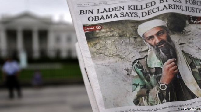 A man takes pictures of the front page of a newspaper featuring a picture of Al-Qaeda leader Osama bin Laden, in front of the White House in Washington, DC, 2 May 2011.