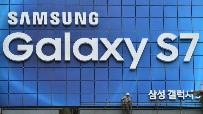 A South Korean worker removes scaffolding after setting up an advertisement billboard for Samsung's Galaxy S7 smartphone installed on top of a building in central Seoul