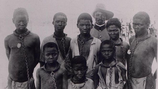Homens e meninos herero acorrentados